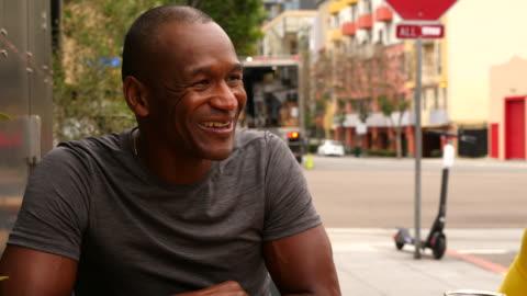 ms smiling mature man sitting with friends at outdoor cafe after morning run - 50 54 år bildbanksvideor och videomaterial från bakom kulisserna