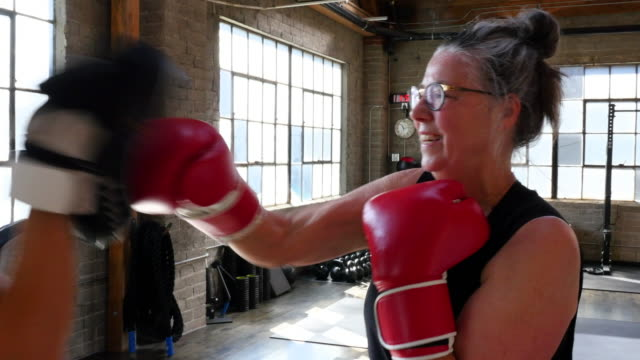 MS PAN Smiling mature woman boxing with coach in gym