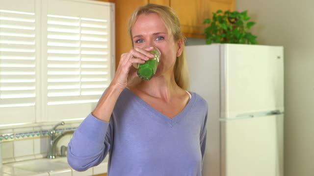 vídeos de stock, filmes e b-roll de smiling mature woman drinking juice - só mulheres maduras