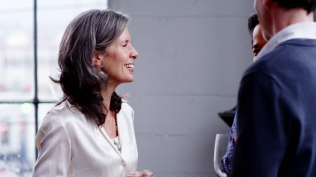 MS smiling mature woman in discussion with friends having drinks at dinner party