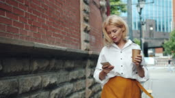 Smiling mature woman is using smartphone holding take out coffee walking outdoors