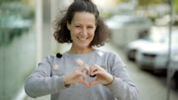Smiling mature woman making heart shape with hands