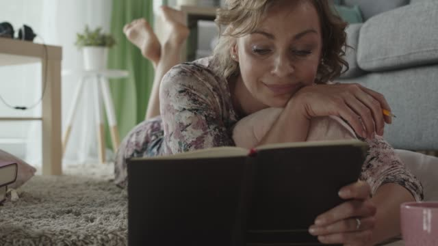 smiling mature woman reading what she wrote in her diary - one mature woman only stock videos & royalty-free footage