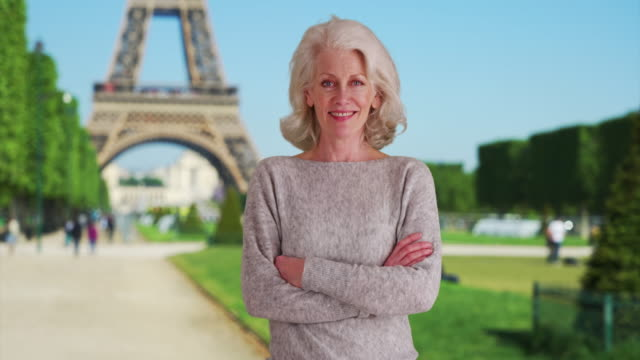 stockvideo's en b-roll-footage met smiling mature woman tourist in front of eiffel tower in paris with crossed arms - monument