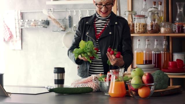 vídeos y material grabado en eventos de stock de sonriendo mujer madura descargando alimentos frescos en su cocina - bolsa reutilizable