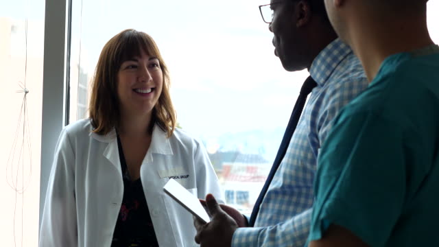 ms smiling medical team in discussion in exam room in hospital - 30 39 years stock videos & royalty-free footage