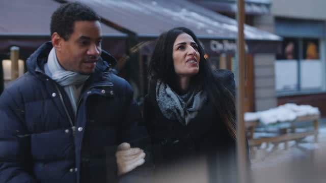 smiling mid adult couple in warm clothing doing window shopping in city - mid adult stock videos & royalty-free footage