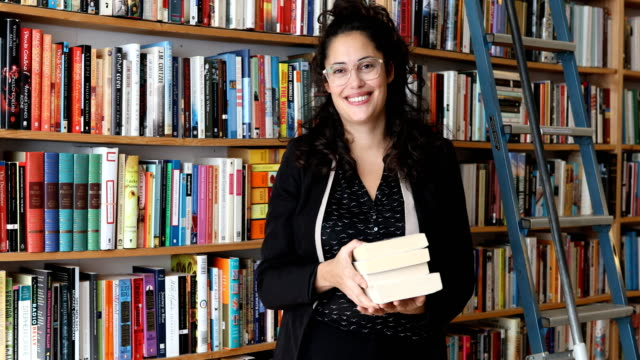 vídeos de stock, filmes e b-roll de smiling mid adult female owner standing with books - livraria