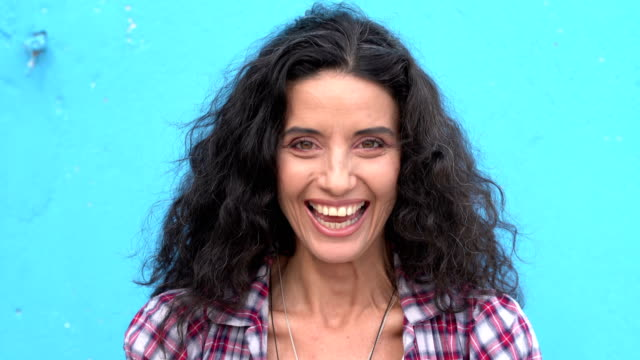 smiling mid adult woman on blue background - coloured background stock videos & royalty-free footage