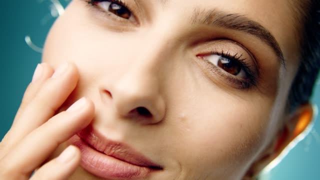 stockvideo's en b-roll-footage met glimlachend midden-oosters etniciteit vrouw huidverzorging. gezichtscrème aanbrengen - vochtinbrengende crème