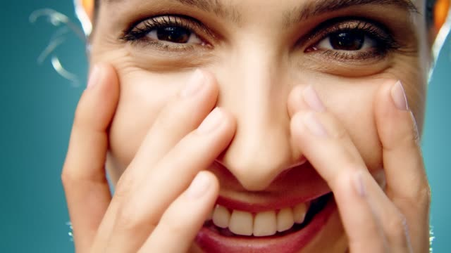 leende mellanöstern etnicitet kvinna hudvård. applicering av ansiktskräm - applicera bildbanksvideor och videomaterial från bakom kulisserna