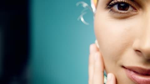 vídeos y material grabado en eventos de stock de sonriente de etnia de oriente medio mujer cuidado de la piel. aplicación de crema facial - monada