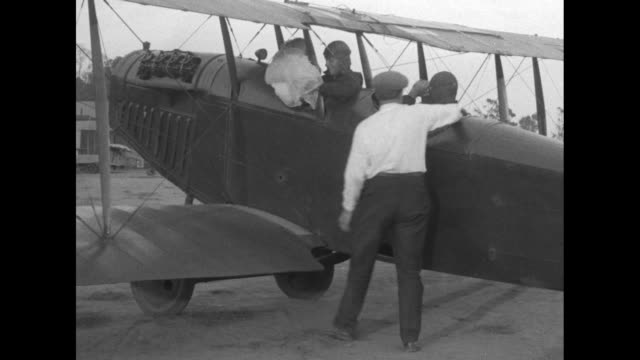 smiling mildred unger wearing a flapper headband blows a kiss / she is carried to a biplane and is placed into a cockpit next to the pilot the plane... - performer stock videos & royalty-free footage