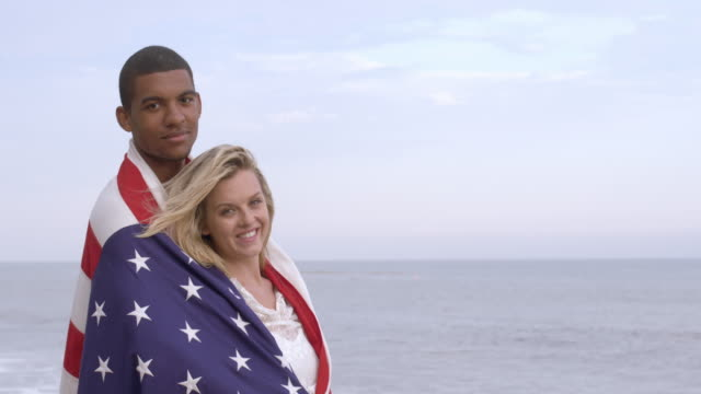 smiling mixed race couple wrapped in us flag at the beach 4k - vesper stock stock videos & royalty-free footage