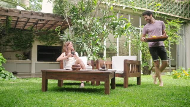 vídeos y material grabado en eventos de stock de sonriendo hombre de raza mixta trayendo bandeja de desayuno al patio trasero - mate técnica de vídeo