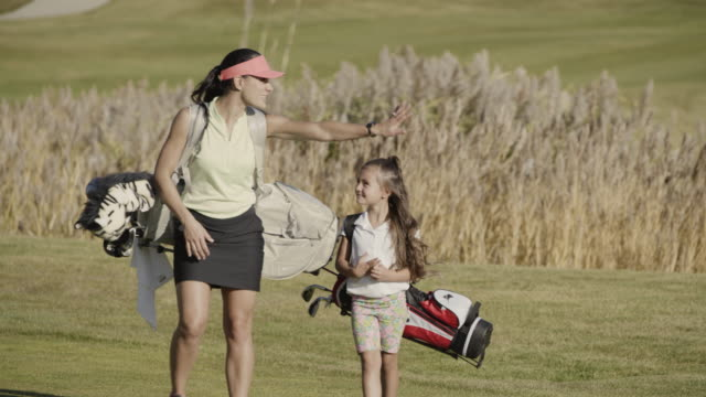 smiling mother and daughter carrying golf bags on golf course / cedar hills, utah, united states - golfer stock videos & royalty-free footage