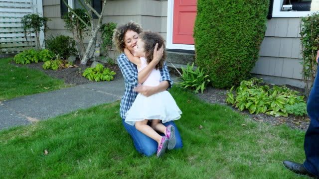 MS Smiling mother and daughter embracing in yard on summer evening
