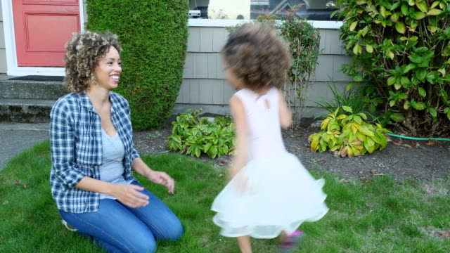 ms smiling mother and daughter embracing in yard on summer evening - trousers stock videos & royalty-free footage