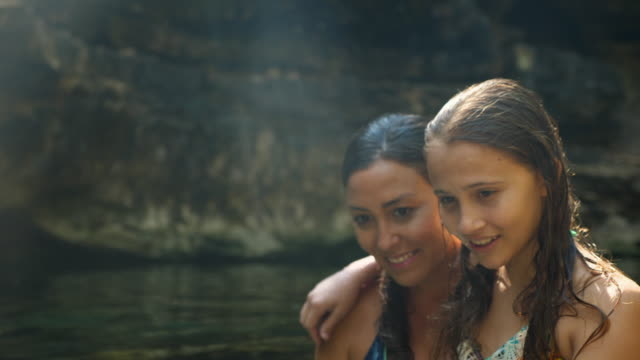 r/f smiling mother and daughter looking in clear water in cenote while exploring on vacation - 30 34 ��r bildbanksvideor och videomaterial från bakom kulisserna