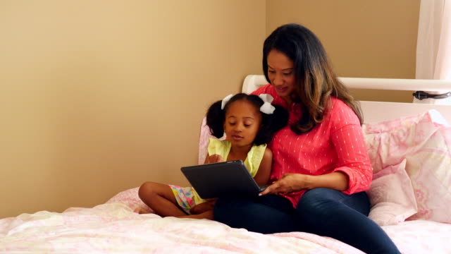 MS Smiling mother and daughter sitting on bed reading book together on digital tablet