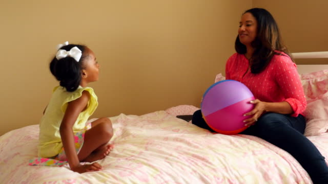 MS ZI Smiling mother and daughter sitting on bed throwing ball back and forth
