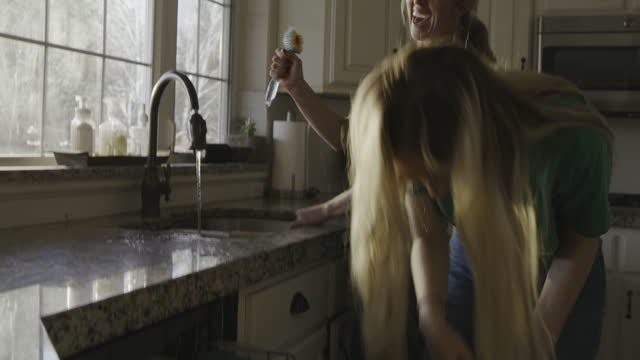 vidéos et rushes de smiling mother and daughter washing dishes and singing to music / highland, utah, united states - lave vaisselle