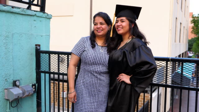ms smiling mother and graduating daughter posing for pictures during celebration meal on restaurant deck - graduation stock videos & royalty-free footage