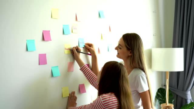 vídeos de stock, filmes e b-roll de 4k que sorri a matriz e a menina que escrevem no papel de nota post-it e que põr a na parede - note pad