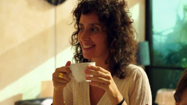 vídeos de stock, filmes e b-roll de cu smiling mother drinking coffee in kitchen - gente comum
