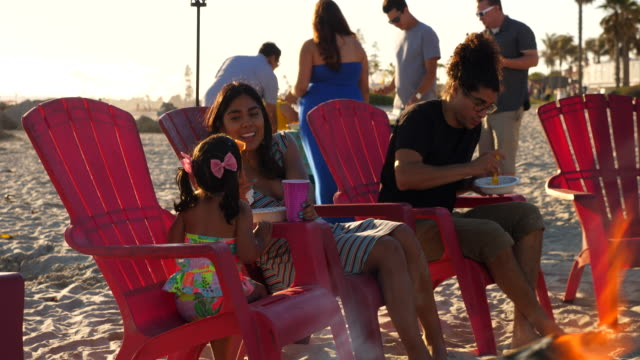 ms smiling mother eating with young daughter during family beach party - pacific islander family stock videos & royalty-free footage