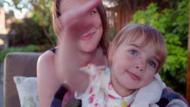 vídeos de stock, filmes e b-roll de ms smiling mother embracing toddler daughter on backyard patio of home - cuidado