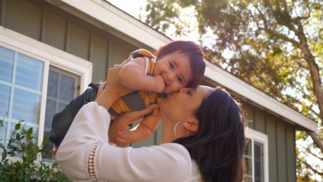 vidéos et rushes de ms smiling mother holding and kissing infant son in front yard of home on summer morning - mise au point au 1er plan