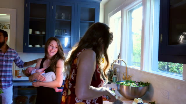 ms ts smiling mother holding newborn baby in discussion with friends making dinner in kitchen - preparing food stock videos & royalty-free footage