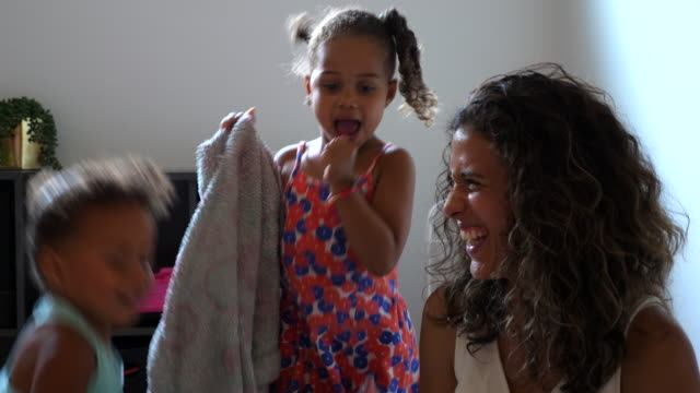 ms smiling mother playing and dancing with daughters in bedroom - happiness stock videos & royalty-free footage