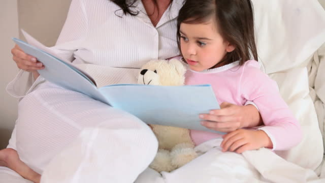 smiling mother reading a book aloud - nightdress stock videos & royalty-free footage