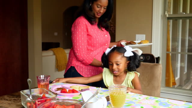 MS Smiling mother sitting down at breakfast table with young daughter