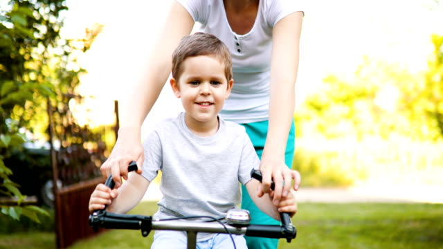 smiling mother teaching her son to ride bicycle in nature - showing stock videos & royalty-free footage