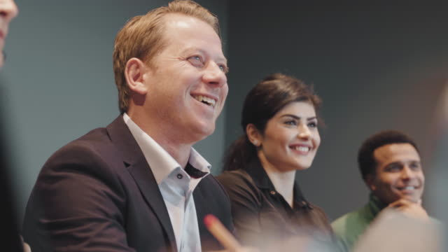 smiling multi-ethnic business colleagues sitting in board room during meeting at workplace - employee engagement stock videos & royalty-free footage