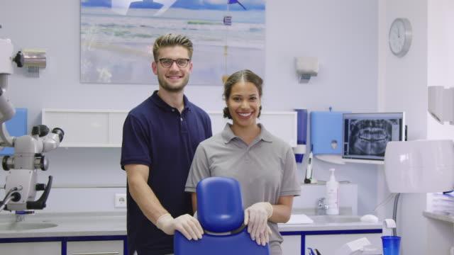 vídeos de stock e filmes b-roll de smiling multi-ethnic dental workers in clinic - dentista