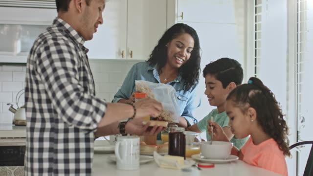 vidéos et rushes de souriant et multiethnique famille prenant son petit déjeuner dans la cuisine à la maison - deux parents