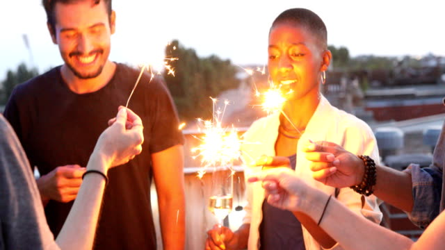 smiling multi-ethnic friends holding sparklers - roof stock videos & royalty-free footage
