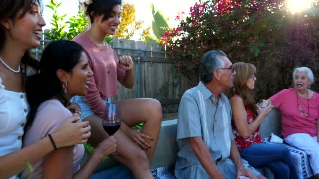 vídeos de stock, filmes e b-roll de pan smiling multigenerational family hanging out together in backyard on summer evening - família de várias gerações