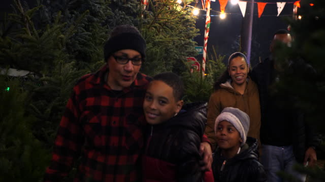 ms smiling multigenerational family walking through christmas tree lot while shopping for tree - warm clothing stock videos & royalty-free footage