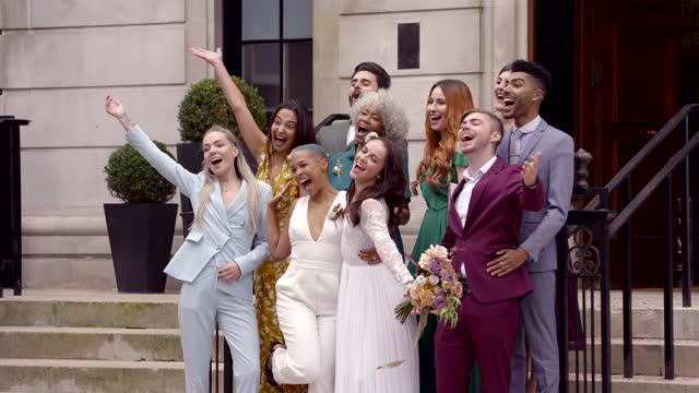 smiling newlywed lesbian couple celebrating their weddinglesbian wedding - multiracial group stock videos & royalty-free footage