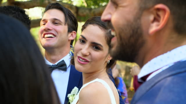 vídeos de stock, filmes e b-roll de ms smiling newlyweds surrounded by friends and family at destination wedding - bride