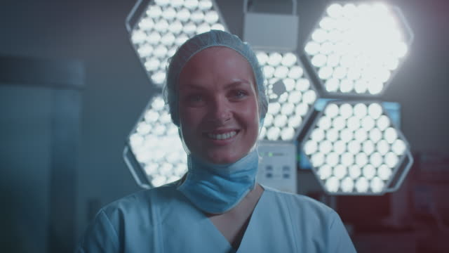 smiling nurse against illuminated surgical light - scrubs stock videos & royalty-free footage