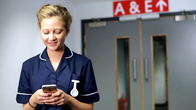 Smiling nurse using cell mobile phone in front of A&E doors in hospital