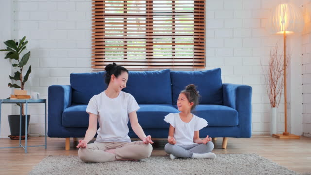 smiling of asian mother and daugther training yoga in living room.exercising, healthy lifestyle, indoors, domestic room, stay at home - saying, family, single mother, relationship, children, homeschooling, leadership, home exercise - two generation family stock videos & royalty-free footage