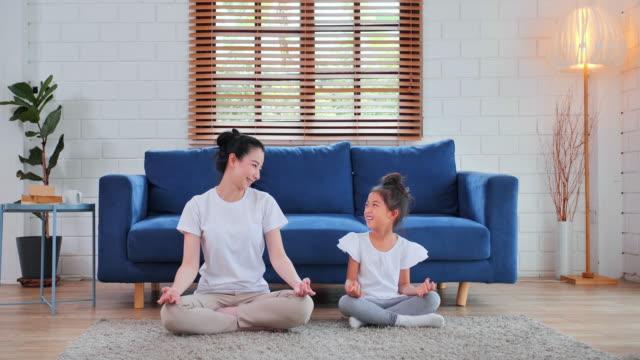 leende av asiatiska mor och daugther utbildning yoga i vardagsrummet. motion, hälsosam livsstil, inomhus, hemrum, stanna hemma - ordstävet, familj, ensamstående mamma, förhållande, barn, hemundervisning, ledarskap, hem träning - förälder och barn bildbanksvideor och videomaterial från bakom kulisserna