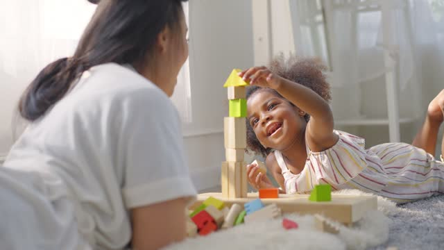 smiling of asian mother with a plastic curler on her hair laying down on the floor playing woodblock toy with african little daughter to finish in living room under the sunlight of morning from a window at home. concept of learning of preschool children. - preschool student stock videos & royalty-free footage